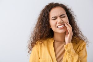 Beautiful young woman suffering from tooth ache on light background